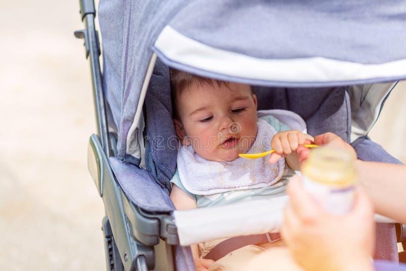 El bebé feliz está comiendo mientras que se sienta en un carro de bebé fotos de archivo