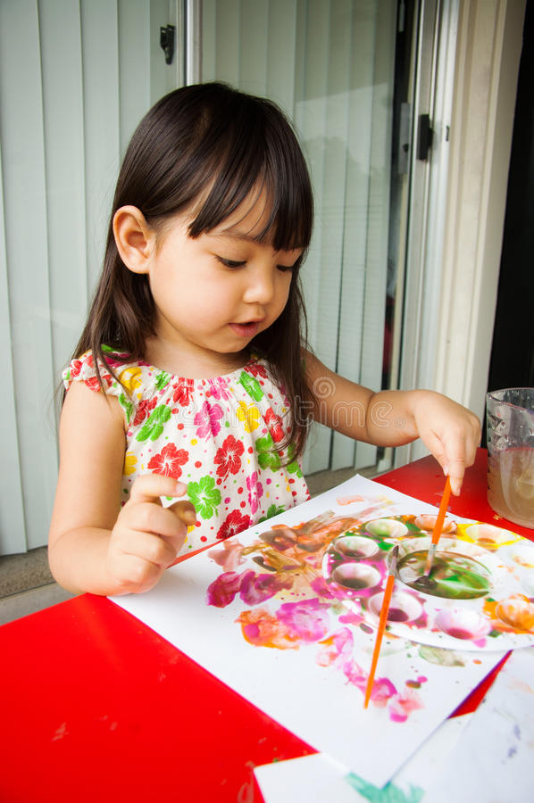 El bebé goza el pintar fotos de archivo