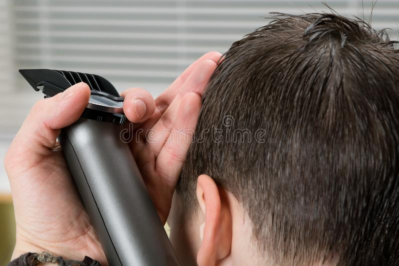 El bebé, hace un corte de pelo, una máquina de afeitar eléctrica más corta, en los peluqueros foto de archivo libre de regalías