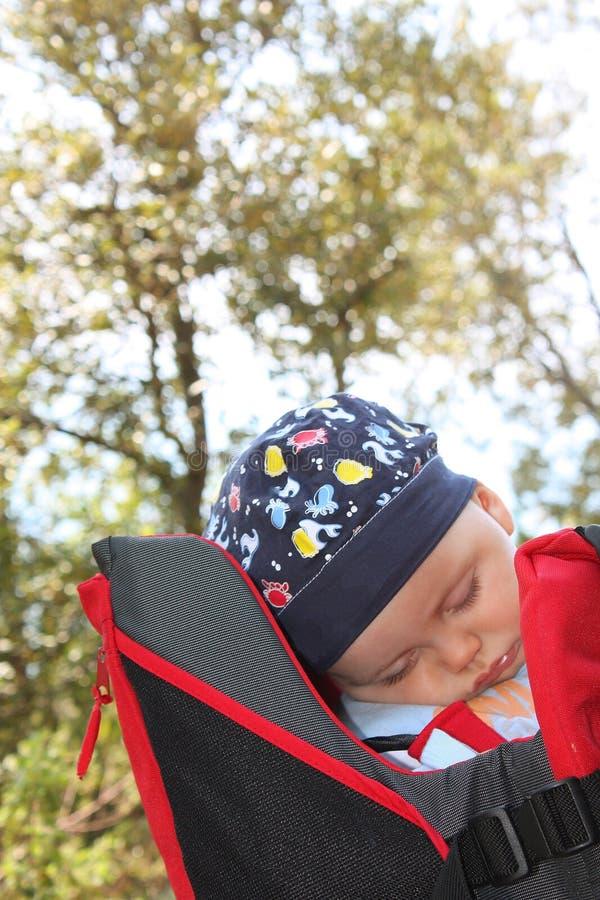 El bebé hermoso duerme al aire libre en un portador de bebé de la mochila foto de archivo
