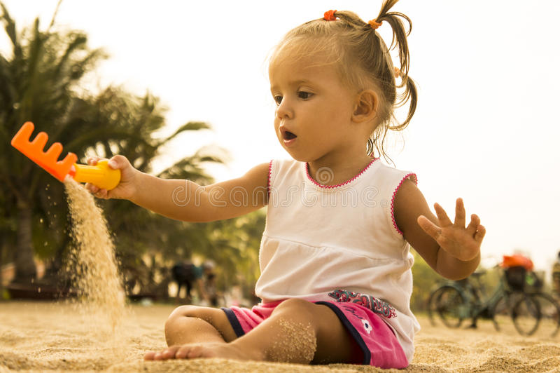 El bebé hermoso se sienta haciendo frente a la cámara y jugando con el rastrillo del juguete en la arena en la playa fotografía de archivo libre de regalías