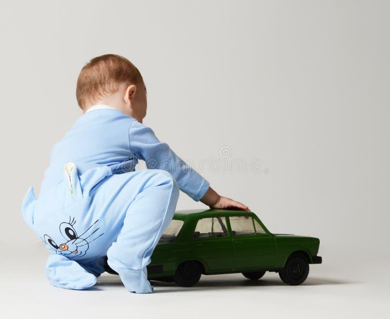 El bebé infantil del niño embroma al niño que se sienta y que juega con el coche retro verde en azul claro y verde fotografía de archivo