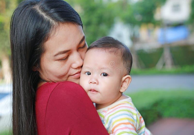El bebé infantil del primer está chupando el finger con llevar asiático de la madre imagenes de archivo