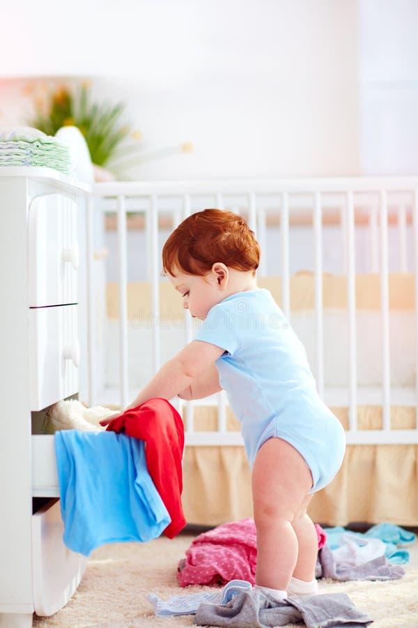 El bebé infantil divertido que lanza hacia fuera viste del aparador en casa imagen de archivo