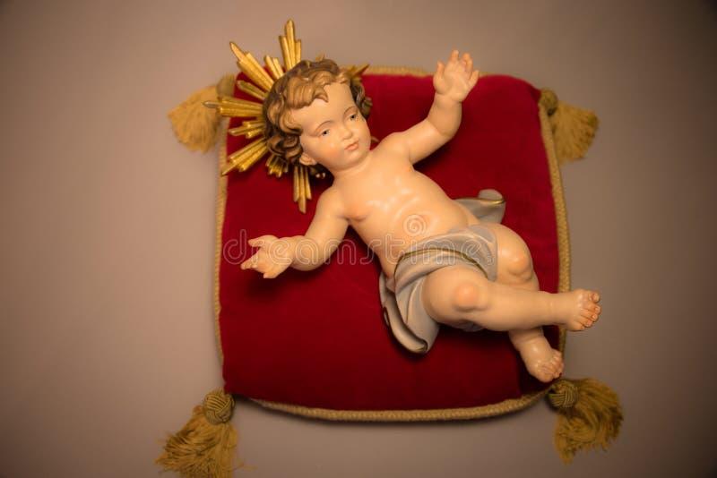 El bebé Jesús de la Navidad con la mano de madera de la aureola talló la colocación en la almohada real con las borlas del oro imágenes de archivo libres de regalías