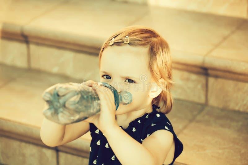 El bebé lindo bebe el agua imagenes de archivo