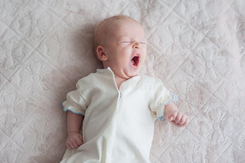 El bebé lindo bosteza en un fondo blanco foto de archivo