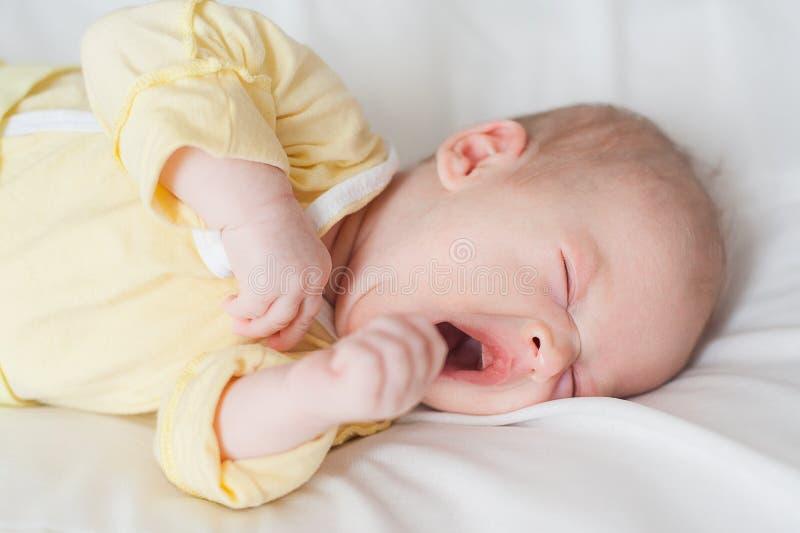 El bebé lindo bosteza en un fondo blanco imagenes de archivo