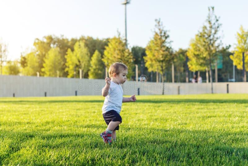 El bebé lindo corre en un césped verde que juega a la puesta al día en naturaleza en un día soleado Niño de un año del concepto y fotos de archivo