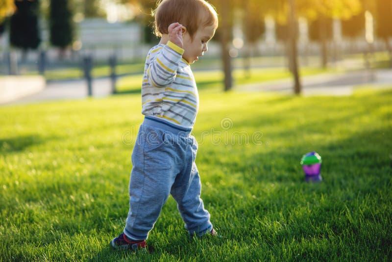 El bebé lindo corre en un césped verde que corre en naturaleza en un día soleado del otoño Niño de un año Primeros pasos del niño imagenes de archivo