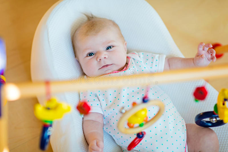 El bebé lindo que juega con el colgante de traqueteo de madera juega imagenes de archivo