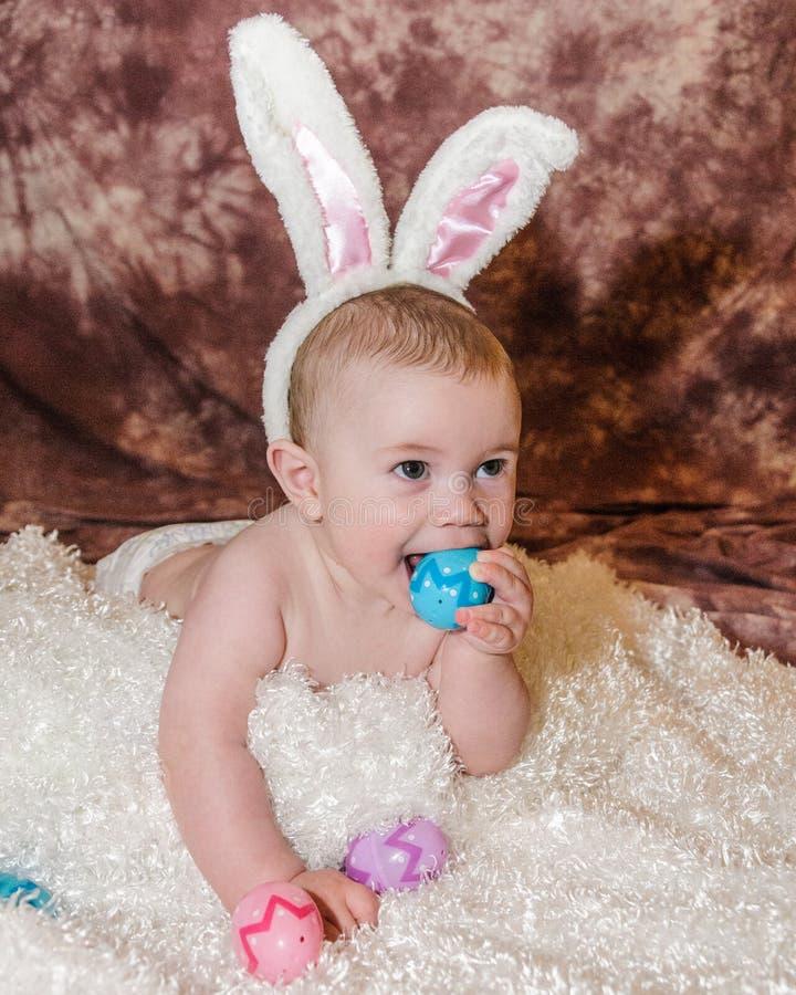 El bebé lleva los oídos del conejito y mastica en el huevo de Pascua plástico fotografía de archivo