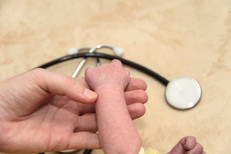 El bebé masculino consigue un examen del pulmón de una enfermera con el estetoscopio imagen de archivo