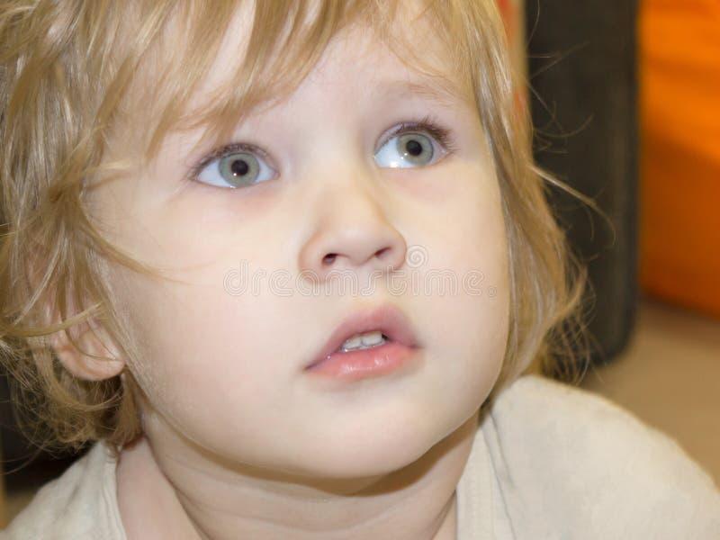 El bebé mira con la pasión y el interés encima y para del lado imagen de archivo
