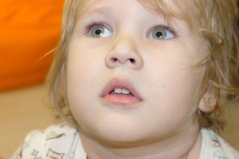 El bebé mira con la pasión y el interés encima y para del lado imagenes de archivo