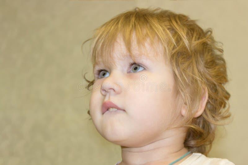 El bebé mira con la pasión y el interés encima y para del lado fotografía de archivo