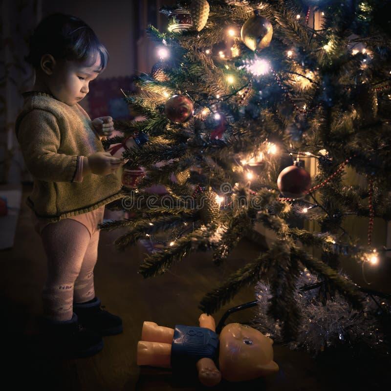 El bebé mira la decoración en un árbol de navidad imágenes de archivo libres de regalías