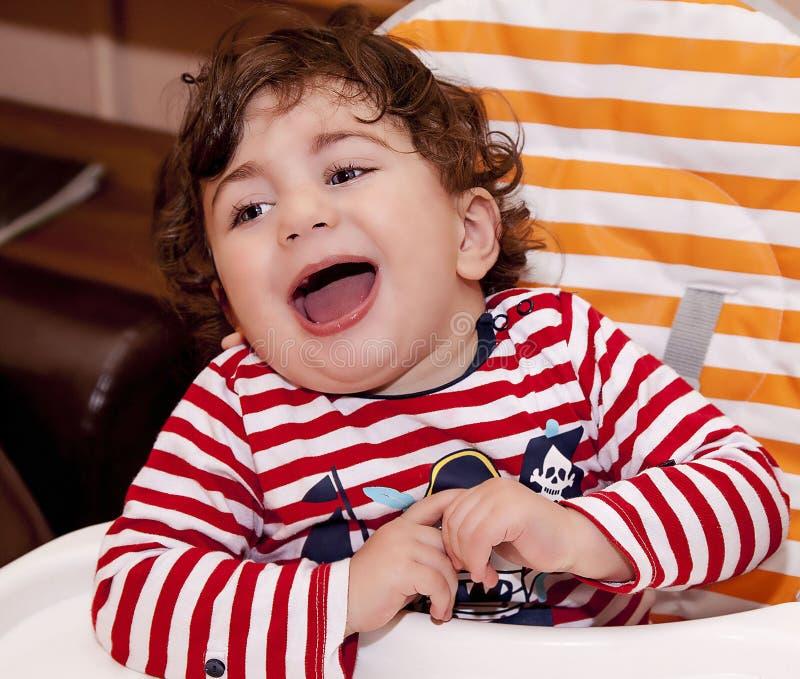 El bebé que el niño se sienta en una risa de la silla de los niños disfruta imagen de archivo libre de regalías