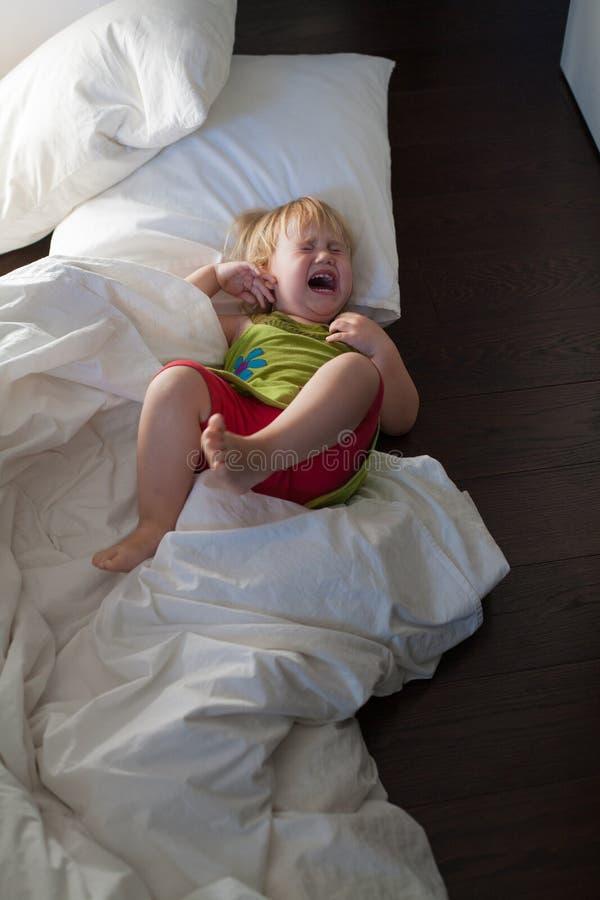 El bebé que grita en cama viste el piso imágenes de archivo libres de regalías