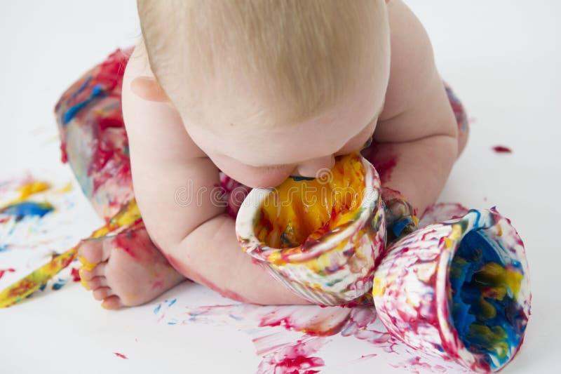 El bebé que juega con hecho en casa fingerpaints foto de archivo