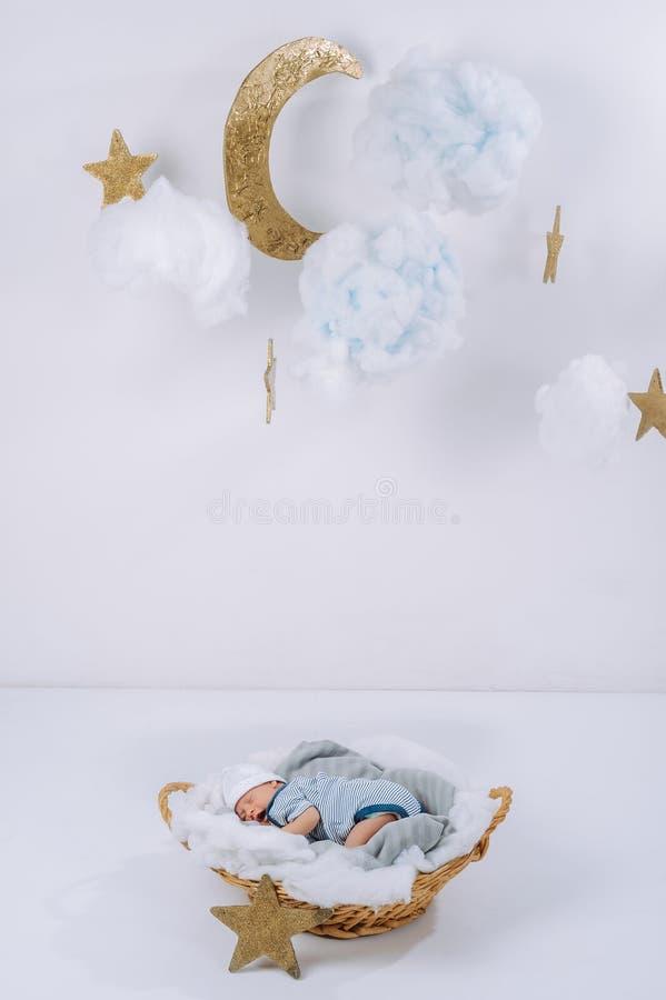 el bebé recién nacido adorable que duerme en cesta con las nubes decorativas está en la luna y las estrellas fotografía de archivo libre de regalías