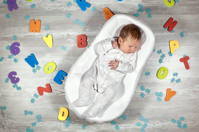 El bebé recién nacido duerme en un capullo ortopédico especial del bebé del colchón, en letras multicoloras de un piso de madera  fotos de archivo libres de regalías
