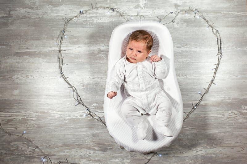 El bebé recién nacido duerme en un capullo ortopédico especial del bebé del colchón, en un piso y un corazón de madera de las gui fotos de archivo