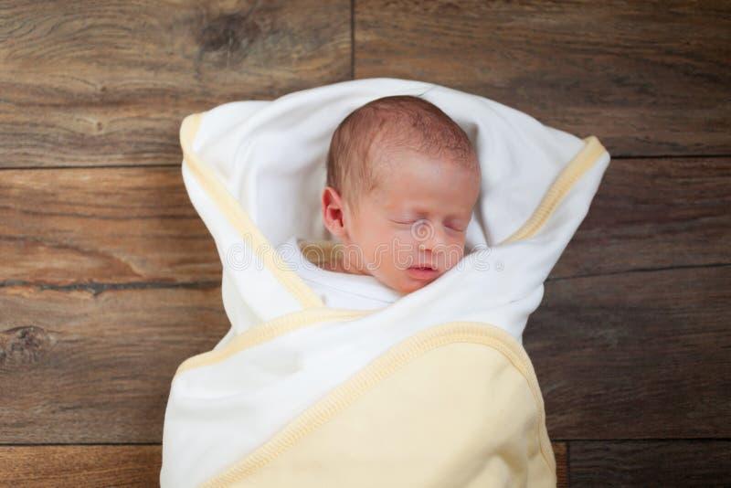 El bebé recién nacido dulce duerme en un fondo de madera marrón Tiro de arriba imagenes de archivo