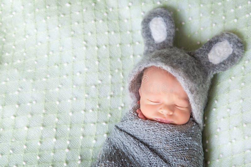El bebé recién nacido durmiente lindo se vistió como el conejito de pascua fotografía de archivo