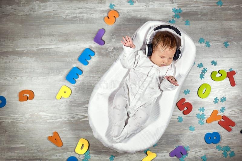 El bebé recién nacido en auriculares duerme en un capullo especial del bebé del colchón, en letras multicoloras de un piso de mad fotos de archivo libres de regalías