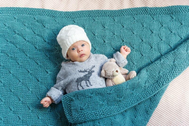 El bebé recién nacido en el casquillo blanco con el juguete del oso de peluche imagen de archivo libre de regalías