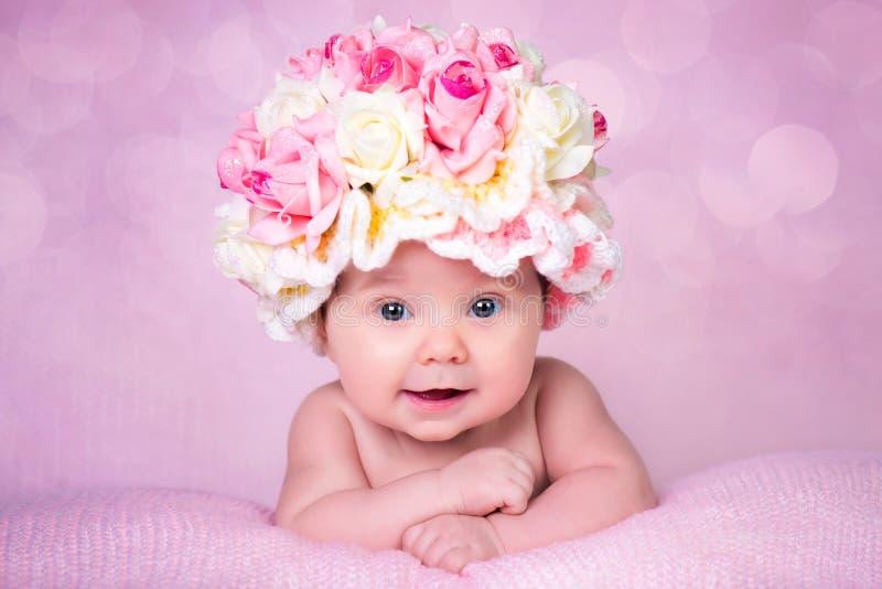 El bebé recién nacido en el sombrero subió las sonrisas Retrato en un fondo rosado foto de archivo libre de regalías