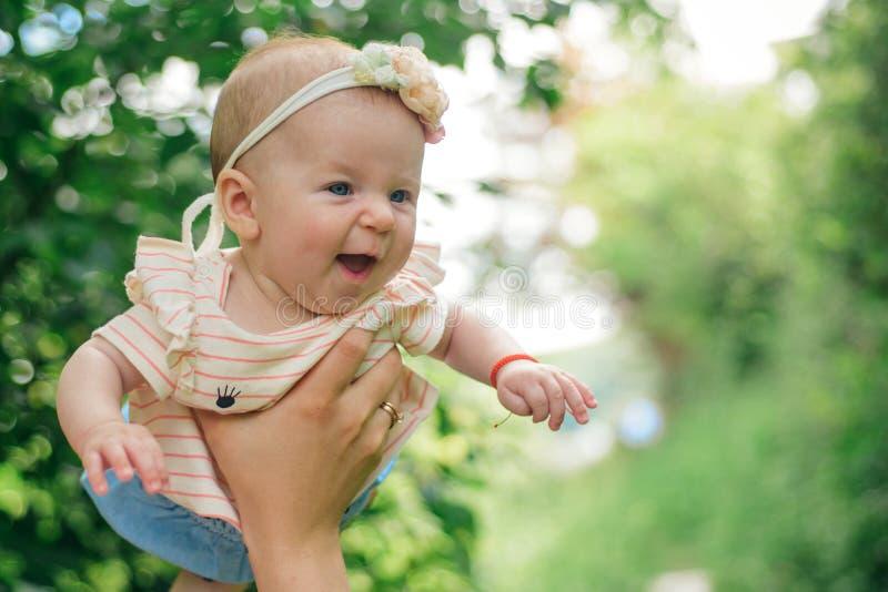El bebé recién nacido goza el volar en manos de los padres Bebé y padre recién nacidos Soy muchacha de los daddys Tengo un día de fotografía de archivo