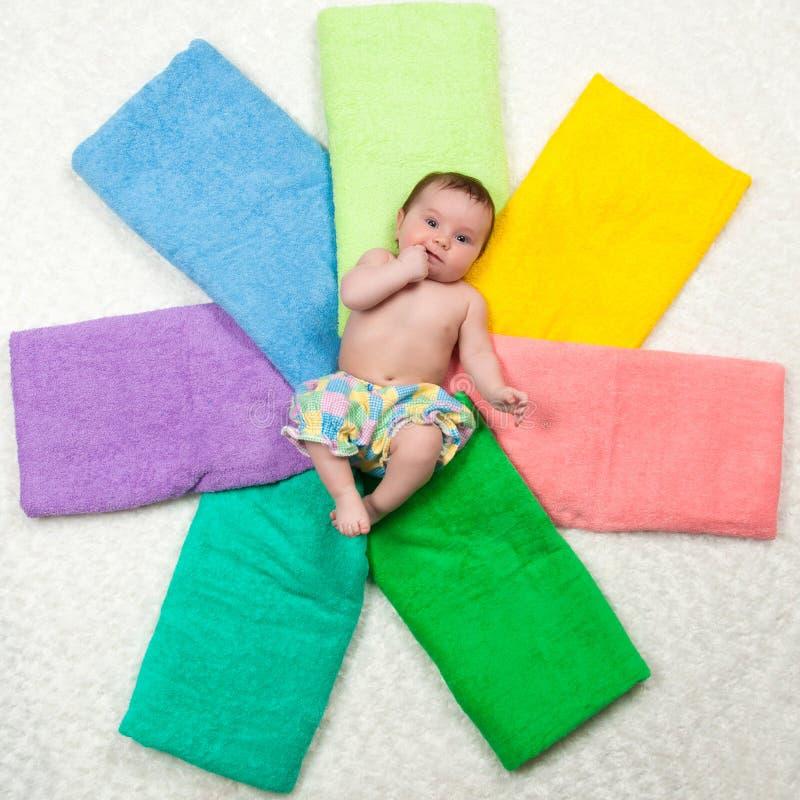 El bebé recién nacido miente en las toallas multicoloras felicidad fotos de archivo