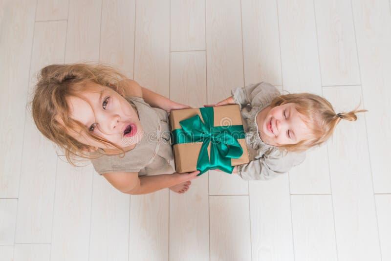 El bebé, regalo de cumpleaños de la muchacha, día de fiesta, la Navidad, fondo blanco de la pared de ladrillo fotografía de archivo libre de regalías