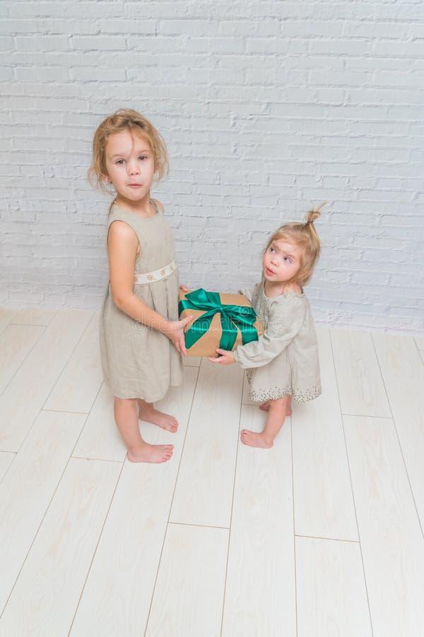 El bebé, regalo de cumpleaños de la muchacha, día de fiesta, la Navidad, fondo blanco de la pared de ladrillo fotos de archivo libres de regalías