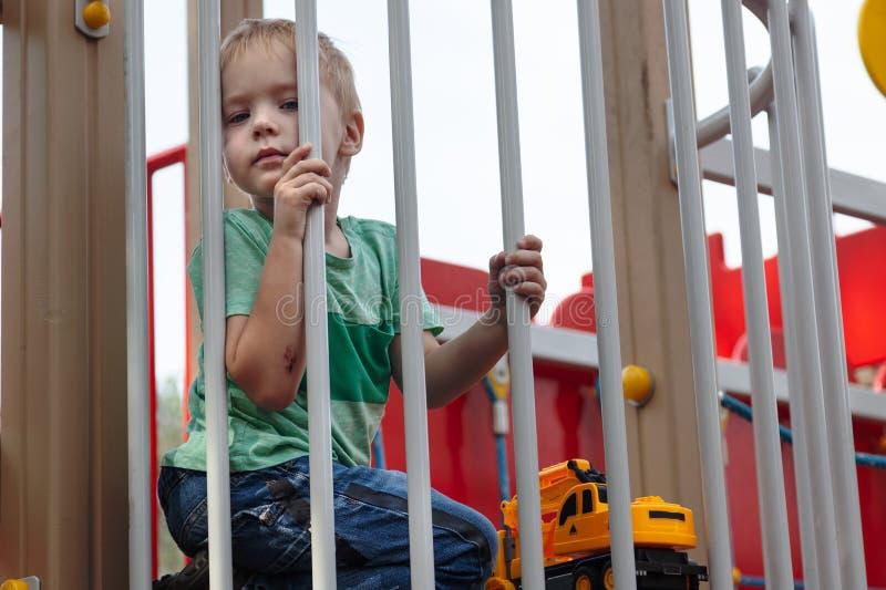 El bebé rubio caucásico lindo se sienta debajo de la cerca del patio de los niños Expresión linda, seria y humile en la cara, str fotografía de archivo