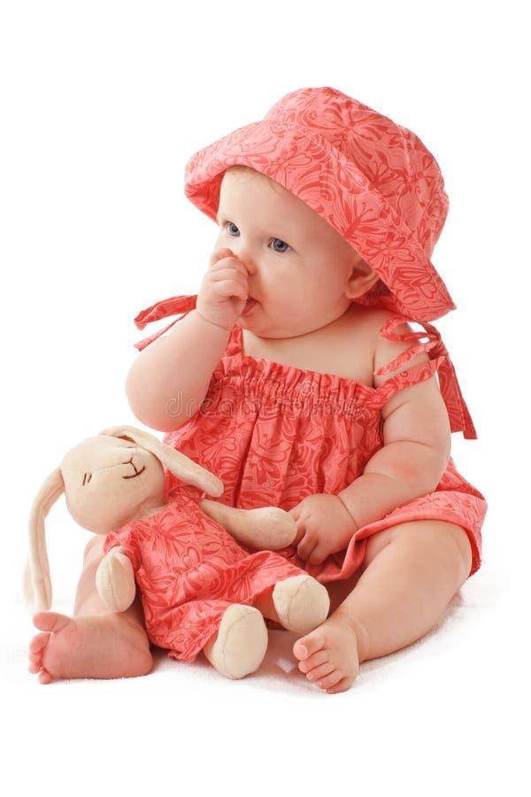 El bebé se sienta con el conejito del juguete y aspira su pulgar imagen de archivo libre de regalías