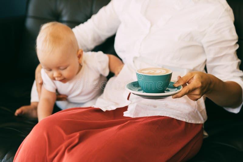 El bebé seis-mes-viejo del niño activo e inquisitivo, mamá se sienta cerca y sostiene una taza de café fotografía de archivo