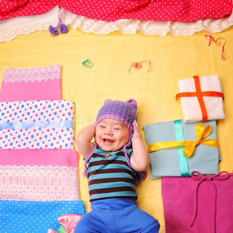 El bebé sonriente celebra su primer cumpleaños y goza de sus regalos imagenes de archivo