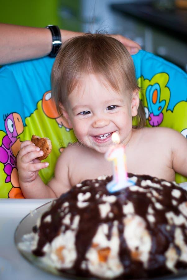 El bebé sopla hacia fuera velas en una torta imagenes de archivo
