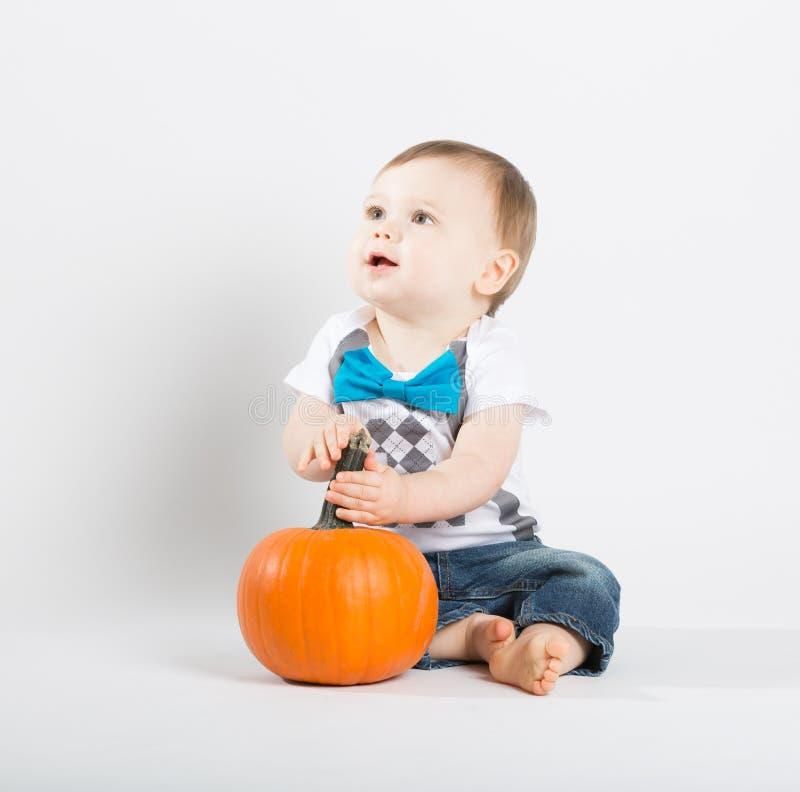 El bebé sostiene la calabaza y mira para arriba apagado a la izquierda foto de archivo libre de regalías