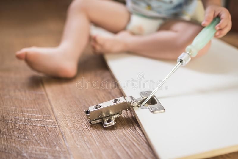 El bebé sostiene un destornillador y repara los muebles imágenes de archivo libres de regalías