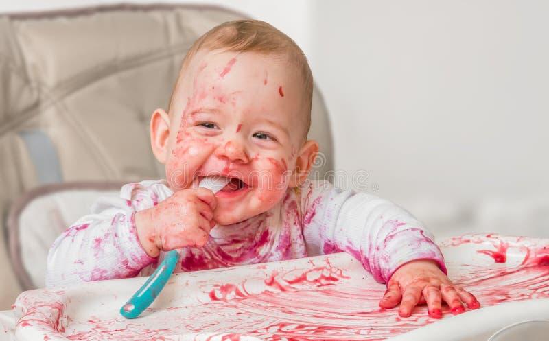 El bebé sucio y sucio está comiendo de la cuchara foto de archivo
