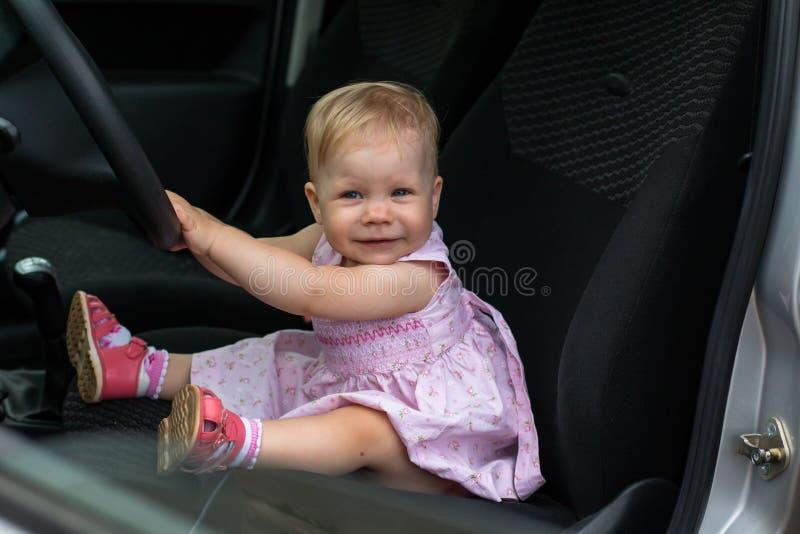 El bebé triste en el coche y las manos del ` s de la mujer están haciendo el st del pelo fotos de archivo