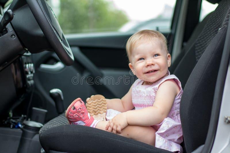 El bebé triste en el coche y las manos del ` s de la mujer están haciendo el st del pelo imágenes de archivo libres de regalías