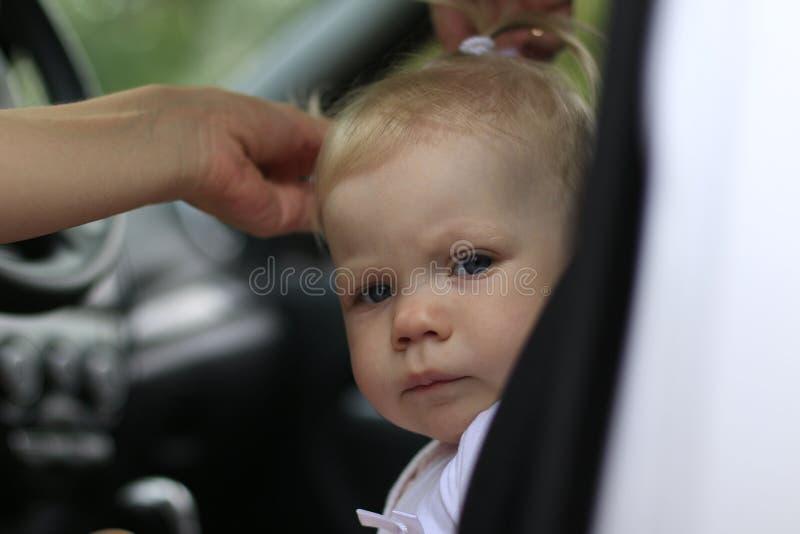 El bebé triste en el coche y las manos del ` s de la mujer están haciendo el st del pelo imagen de archivo