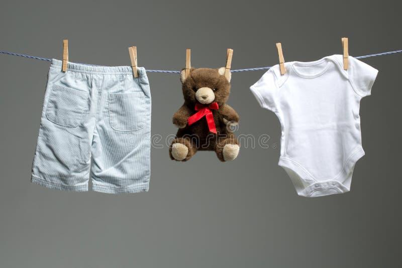 El bebé viste, un peluche refiere la cuerda para tender la ropa imagenes de archivo