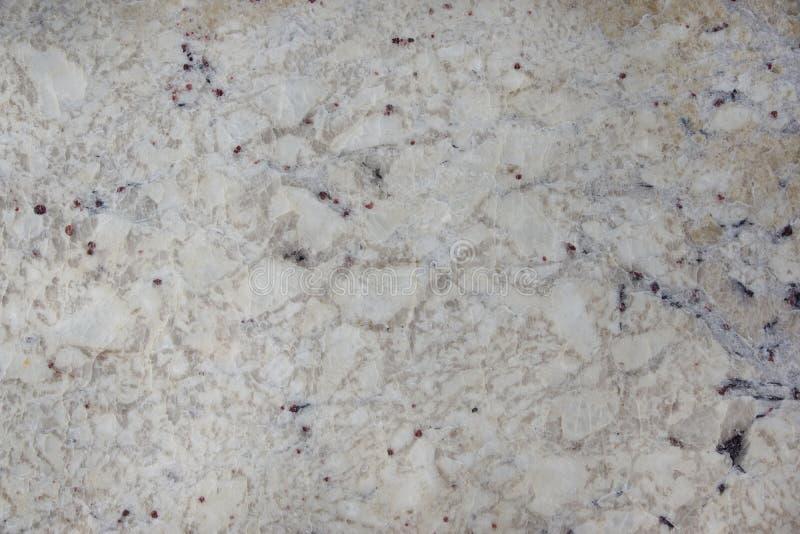 El beige natural de la piedra del fondo con las motas oscuras llamó el granito Bianco Romano fotografía de archivo