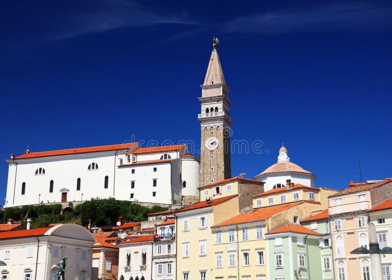 El belltower de la iglesia del ` s de San Jorge y el monasterio franciscano próximo, vistos del cuadrado de Tartini en Piran foto de archivo